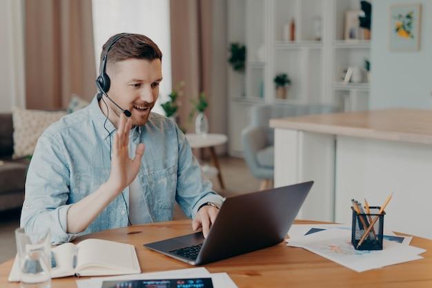 Улыбающийся мужчина-фрилансер, работающий дома и использующий гарнитуру, смотрит на экран ноутбука и здоровается, машет кому-то и улыбается, сидит перед компьютером и ведет видеозвонок