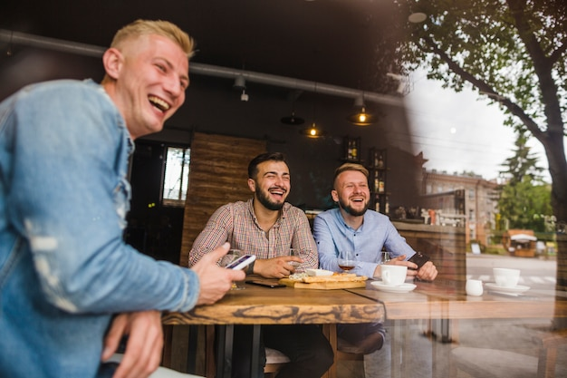Smiling male friends enjoying in the restaurant