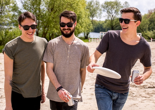 Smiling male friends in sunglasses walking on beach