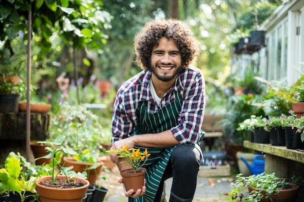 Улыбающийся мужчина садовник держит растение в горшке