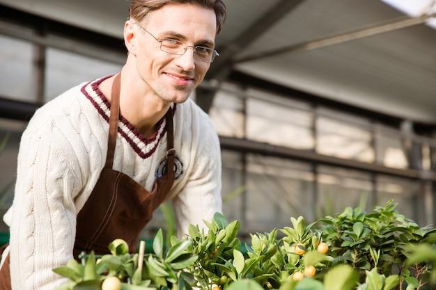 ガーデン センターで働く茶色のエプロンと眼鏡をかけた笑顔の男性庭師