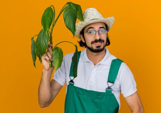 ガーデニング帽子をかぶって光学メガネで笑顔の男性の庭師は植物を保持します