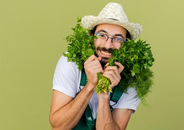 Il giardiniere maschio sorridente in vetri ottici che porta il cappello di giardinaggio tiene il finocchio e il coriandolo