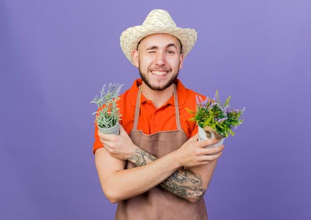 Smiling male gardener wearing gardening hat blinks eye and crosses arms holding flowerpots