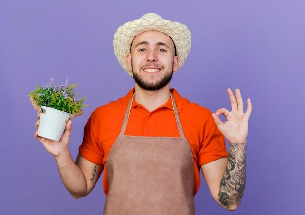 원예 모자를 쓰고 웃는 남성 정원사 제스처 확인 손 기호 및 화분 보유