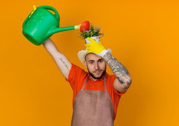 Il giardiniere maschio sorridente che porta il cappello di giardinaggio tiene il vaso di fiori sopra la testa che finge di annaffiare con l'annaffiatoio