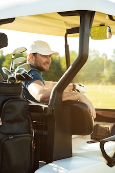 Smiling male golfer sitting in a golf cart