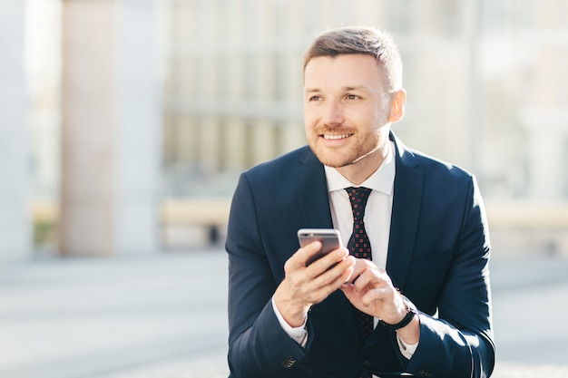 Smiling male manager with appealing look, dressed formally and uses modern smart phone