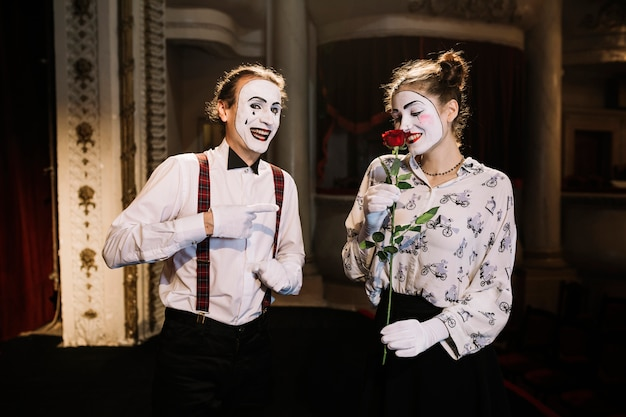 Smiling male mime artist pointing at female mime smelling red rose