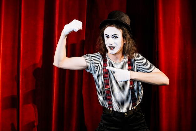 Smiling male mime pointing finger toward flexing muscle