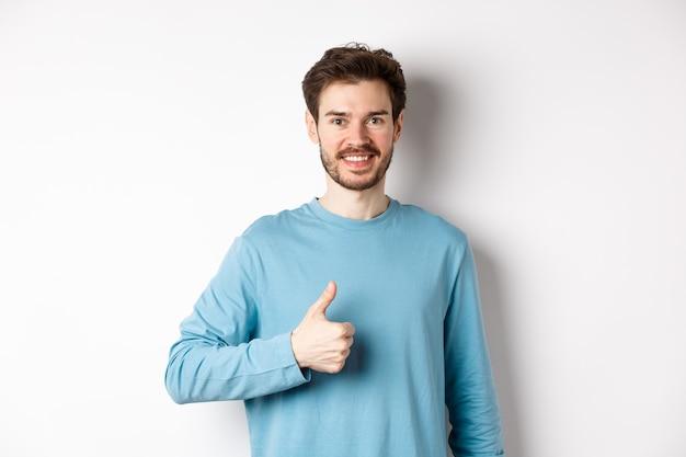 親指を立てて、製品を承認して推奨し、優れた選択を賞賛し、白い背景の上に立っているカジュアルなシャツの笑顔の男性モデル