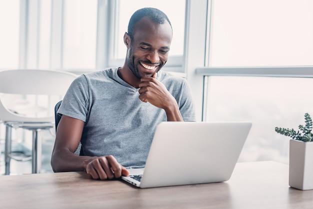 笑顔の男性レストラン経営者は、財務報告を行い、オンラインショッピングを行い、レストラン向けの製品を購入し、年間の数値を調査し、利益を分析します。企業の所有者が銀行口座のステータスを確認します