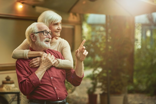 Smiling male retiree in glasses pointing finger to the side and embracing with his wife