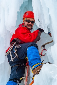 Smiling male rock climber with ice ax among icicles of a frozen waterfall