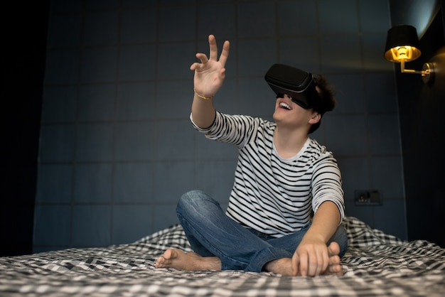 Smiling male sitting on bed using vr glasses