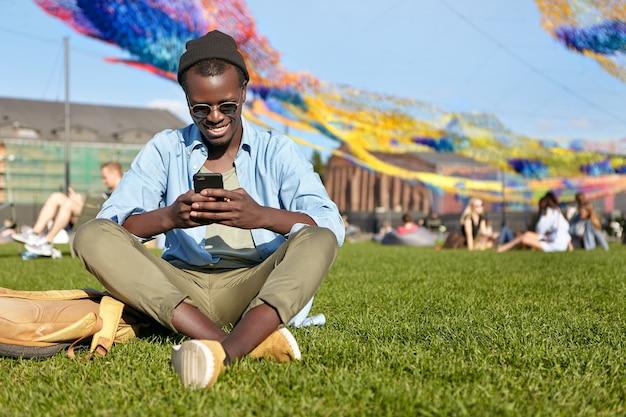 座っている笑顔の男性が緑の芝生に足を組んだ