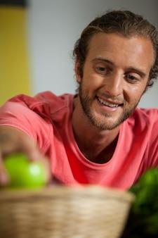 Улыбающийся мужской персонал, собирающий фрукты в разделе органических продуктов