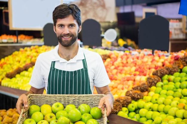 スーパーで青リンゴのバスケットを持って笑顔の男性スタッフ