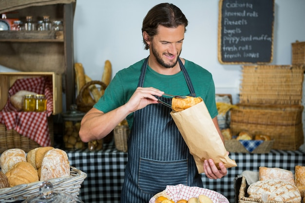 Smiling male staff packing bread in paper bag