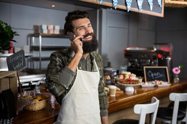커피 숍 카운터에서 휴대 전화로 이야기하는 남성 직원 미소
