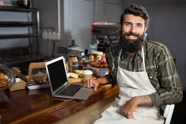 베이커리 숍 카운터에서 노트북을 사용하는 남성 직원 미소