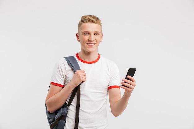Улыбающийся ученик с чистой здоровой кожей, носить повседневную одежду и рюкзак, держа смартфон, изолированных на белом
