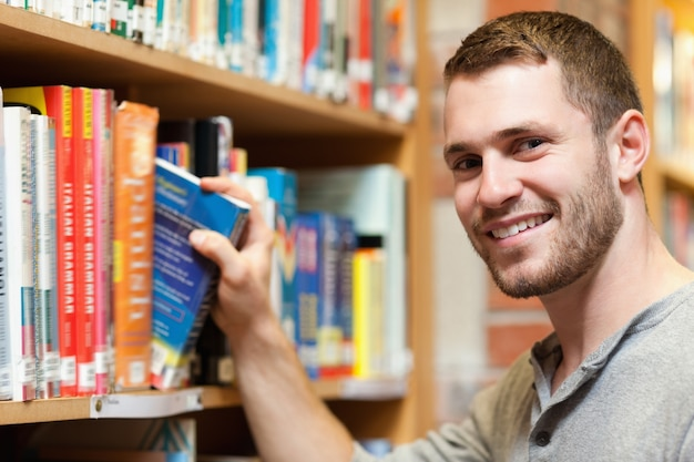 Smiling male student picking a book