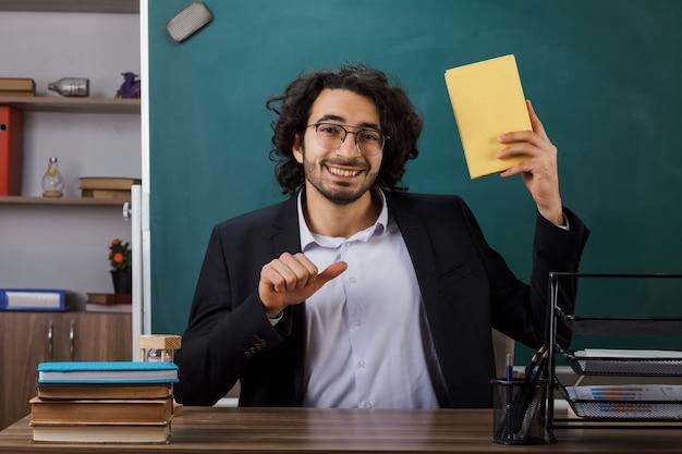 Insegnante maschio sorridente con gli occhiali che tiene e indica il libro seduto al tavolo con gli strumenti della scuola in classe