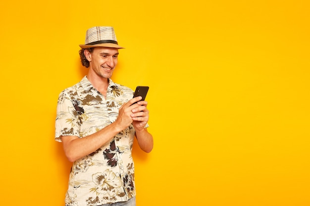 Smiling male tourist on vacation with phone in his hands writes message isolated yellow background