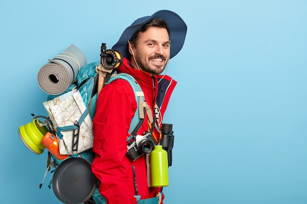 Smiling male tourist wears hat and red jacket, carries rucksack with map, karemat, uses binoculars, flask with hot drink