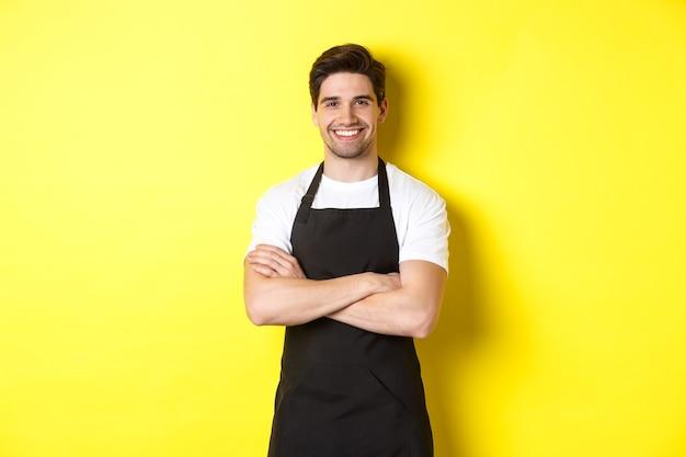 Улыбающийся официант в черном фартуке уверенно стоит, скрестив руки на груди у желтой стены