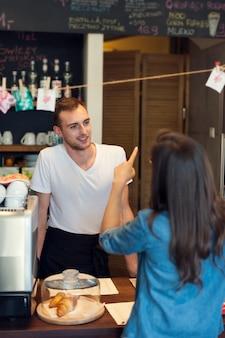 Улыбающийся официант-мужчина получает заказ от молодой женщины