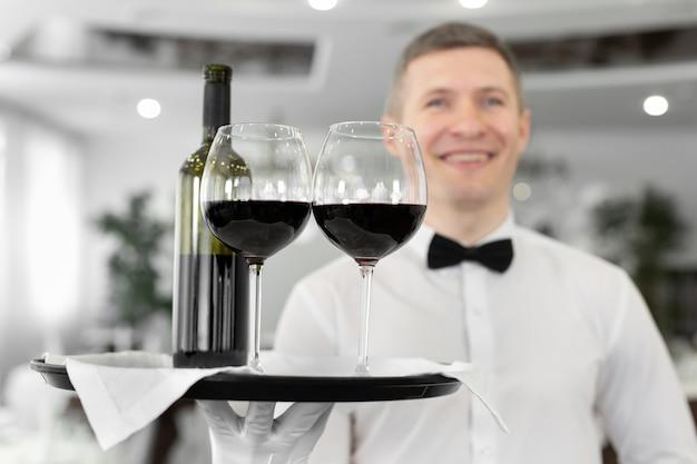 Улыбающийся мужчина-официант с бокалами красного вина и бутылкой на подносе в ресторане.