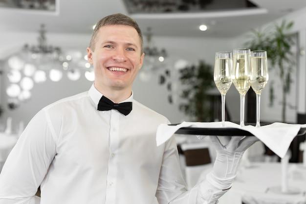 Улыбающийся официант-мужчина с бокалами белого вина на подносе в ресторане.