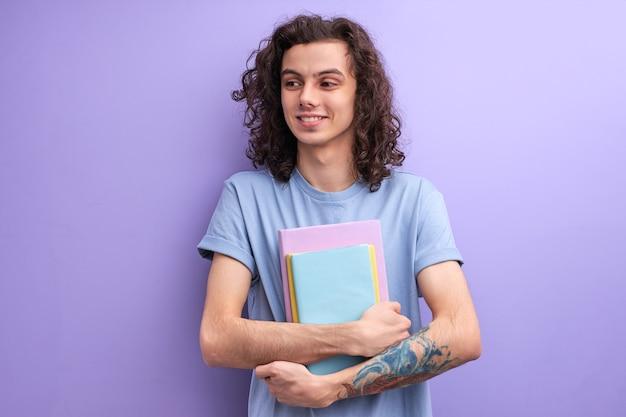 本を手に持って、大学に行く長い巻き毛の男性の笑顔
