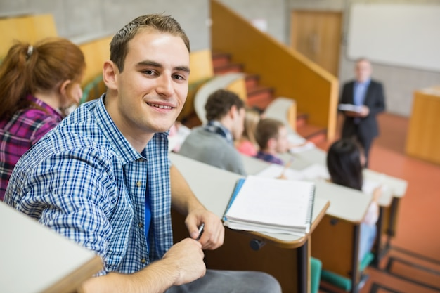 Smiling male with students and teacher at lecture hall