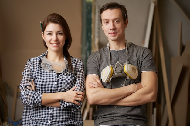 Smiling male and woman joiners with arms crossed looking at camera in workshop