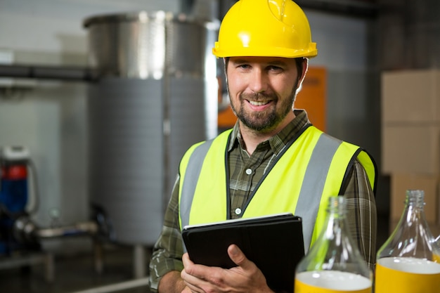 Smiling male worker holding digital tablet in factory