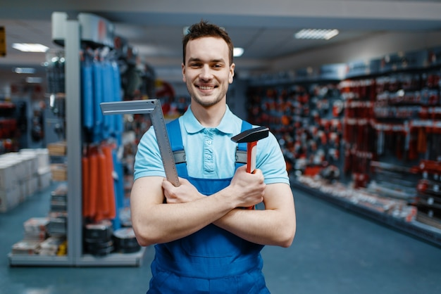 유니폼을 입고 웃는 남성 노동자는 도구 저장소에 망치와 모서리를 보유