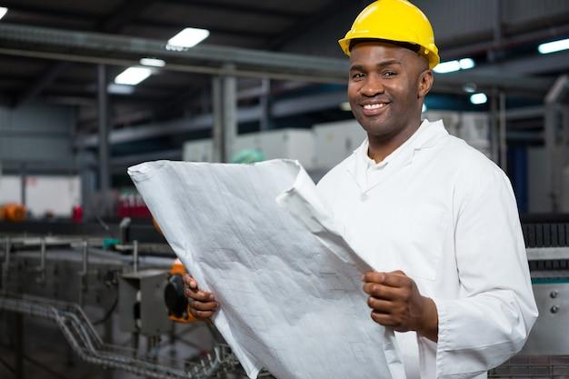 Sorridente lavoratore di sesso maschile che legge le istruzioni alla fabbrica di succhi
