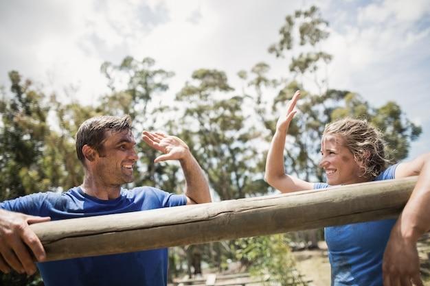 Улыбающиеся мужчина и женщина дают пять, опираясь на препятствие во время полосы препятствий