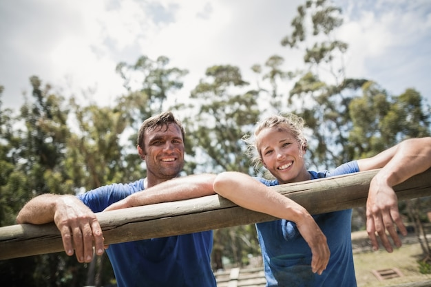 Улыбающиеся мужчина и женщина, опираясь на препятствие во время полосы препятствий в учебном лагере