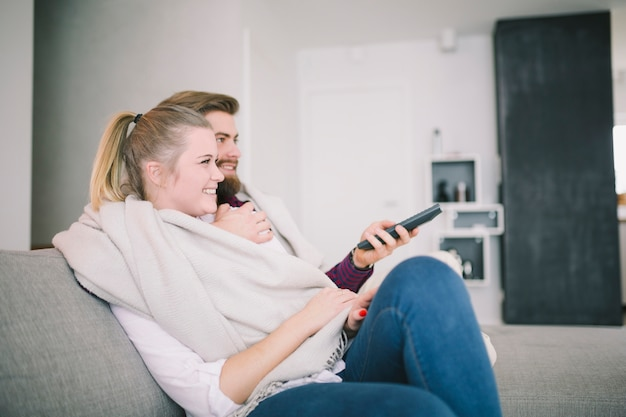 Улыбающиеся мужчина и женщина смотреть телевизор