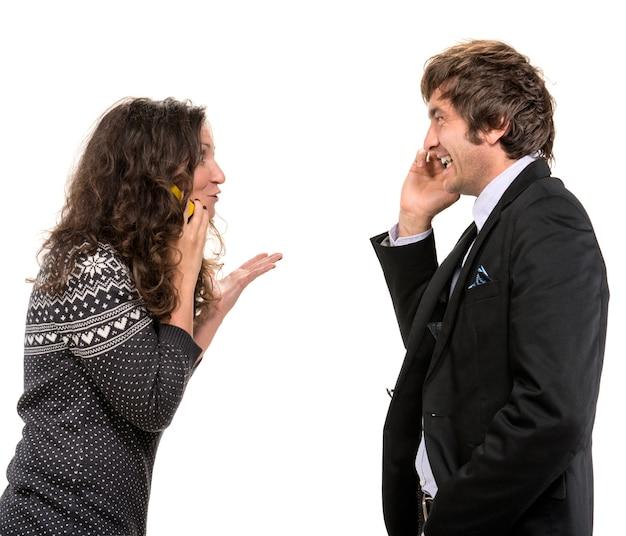 Улыбающийся мужчина и женщина с мобильными телефонами на белой стене