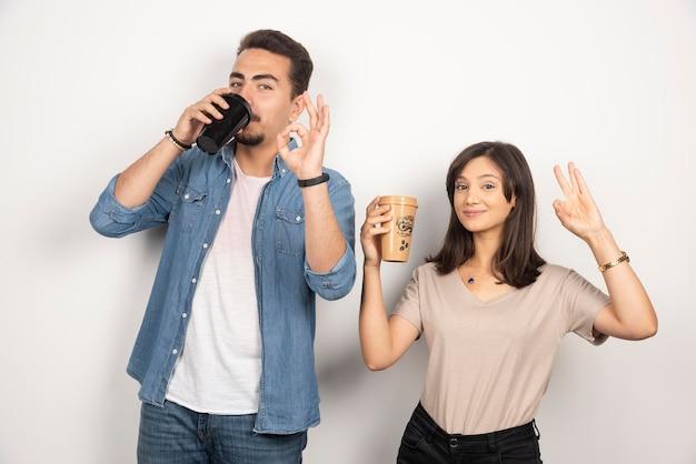 Улыбающийся мужчина и женщина с чашками кофе.