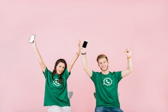 Smiling man and woman with mobile phone raising their arms over pink background