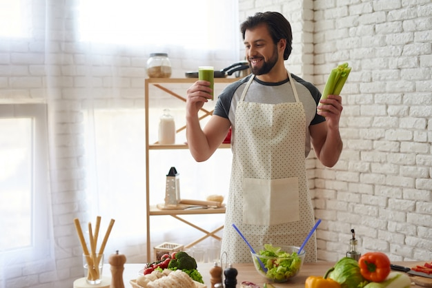 Smiling man in apron prepares cocktail of celery.