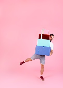 Smiling man balancing with stack of colorful gift boxes against pink background