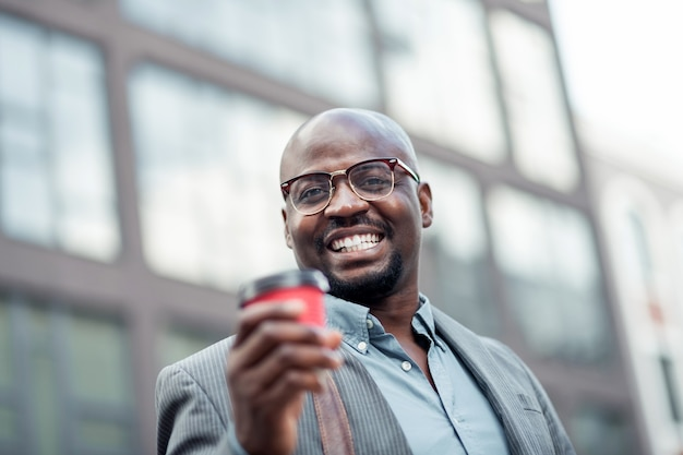 Smiling man. bearded african-american office worker wearing glasses smiling and drinking coffee
