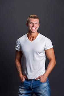 Smiling man in blank tshirt on gray wall